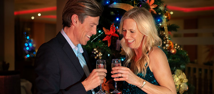 A couple drinking by a Christmas tree