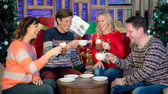 Group drinking coffe next to a Christmas tree