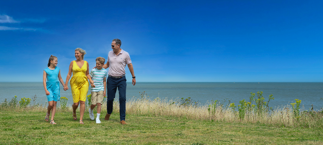 Family enjoying walk along coast